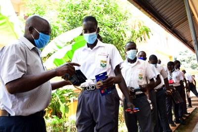 Invigilators check students at Kibuli Secondary School in Kampala, Uganda, before their examinations on March 1, 2021 (file photo).