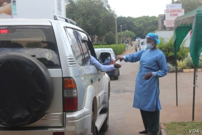 A health official disinfects people arriving at Wilkins Hospital, in Harare, May 12, 2021.