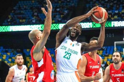 Ivory Coast's Cedric Bah, centre, attempts to make a basket against Tunisia during the final match of the 2021 Fiba AfroBasket Championship at Kigali Arena in Rwanda on September 5, 2021.